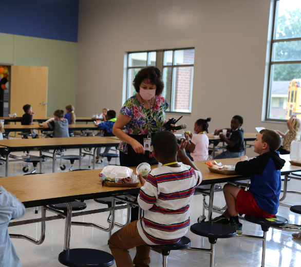 Elementary students eating lunch in cafeteria- socially distanced